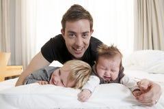 Het jonge vader spelen met zoete babymeisje en zoon Royalty-vrije Stock Afbeeldingen