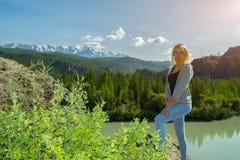 Het jonge verblijf van het blondemeisje op een rots op de zonnige warme de herfstzomer D royalty-vrije stock afbeeldingen