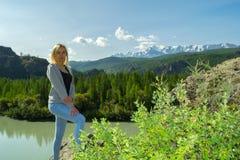 Het jonge verblijf van de blondevrouw op een rots op de zonnige warme de herfstzomer royalty-vrije stock foto