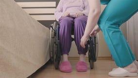 Het jonge verpleegster geven van oudere gehandicapte vrouw in rolstoel en overdrachten haar in bed