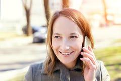 Het jonge volwassen gelukkige Kaukasische wooman glimlachen terwijl in openlucht het spreken van smartphone stock foto's