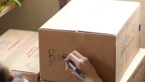 Het jonge volwassen schrijven op een bewegende doos stock video