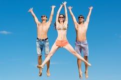 Het jonge vrienden springen Stock Foto's