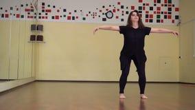 Het jonge vrij expressieve meisje dansen De mannequin met lange haren beweegt het lichaam bij studio stock videobeelden