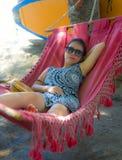 Het jonge vrij gelukkige Aziatische Chinese vrouw liggen lui op de zonbed van de strandhangmat ontspande en vrolijk in de reis va stock afbeelding