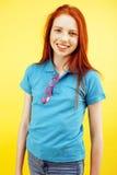 Het jonge vrij rode het meisje van haar tienerhipster stellen in glazen het emotionele gelukkige glimlachen op gele achtergrond,  Royalty-vrije Stock Afbeelding