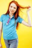 Het jonge vrij rode het meisje van haar tienerhipster stellen in glazen het emotionele gelukkige glimlachen op gele achtergrond,  Stock Fotografie