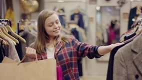 Het jonge vrij vrouwelijke klant zoeken nieuwe kleren in een kleding slaat holding het winkelen zakken op stock video