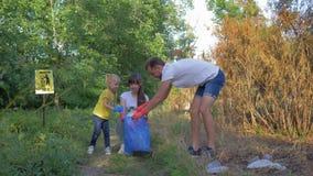 Het jonge vrijwilligersmannetje en het wijfje met de zorgen van het kindmeisje over ecologie milieu en verzamelen plastic residu' stock videobeelden