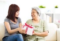 Het jonge vrouw aanwezige geven aan grootmoeder stock foto's