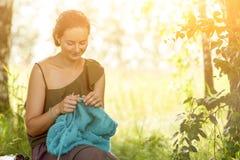 Het jonge vrouw breien in bos Stock Foto