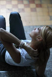 Het jonge vrouw doen leunen op de treden Royalty-vrije Stock Foto