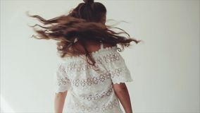 Het jonge vrouw donkerbruine stellen in studio op witte achtergrond en het lopen aan camera stock footage