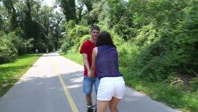 Het jonge vrouw en man rollerblading op een zonnige dag in park, die handen houden stock videobeelden