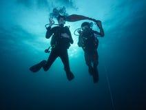 Het jonge vrouw en man scuba-duikers onderzoeken stock afbeelding