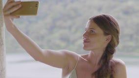 Het jonge vrouw gebruiken mobiel voor selfiefoto op meer en regenwoudlandschap Reizend meisje die selfie door smartphone nemen stock footage