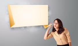 Het jonge vrouw gesturing met de moderne ruimte van het origamiexemplaar Royalty-vrije Stock Foto's
