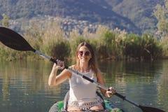 Het jonge vrouw kayaking op het meer stock foto's