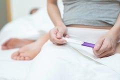 Het jonge vrouw kijken toont ter beschikking bij het controleren van de uitrusting van de zwangerschapstest royalty-vrije stock foto