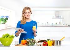 Het jonge vrouw koken in een moderne keuken Royalty-vrije Stock Afbeeldingen
