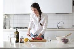 Het jonge vrouw koken in haar keuken royalty-vrije stock afbeeldingen