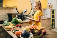Het jonge vrouw koken op recepten, gezond ecovoedsel stock afbeeldingen
