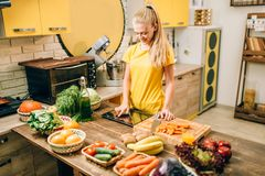 Het jonge vrouw koken op recepten, gezond voedsel stock afbeelding
