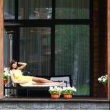 Het jonge vrouw leggen sunbed Stock Foto