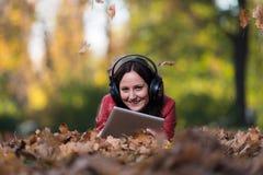 Het jonge Vrouw Liggen Buiten en het Luisteren aan Hoofdtelefoons royalty-vrije stock afbeelding