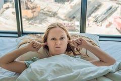 Het jonge vrouw liggen op een bed behandelde haar oren wegens het lawaai In het venster na het bed kunt u zien royalty-vrije stock foto