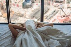 Het jonge vrouw liggen op een bed behandelde haar oren wegens het lawaai In het venster na het bed kunt u zien stock fotografie