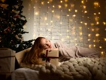 Het jonge vrouw liggende dromen dichtbij magische Nieuwe jaargiften door een Kerstboom Royalty-vrije Stock Afbeelding