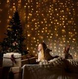 Het jonge vrouw liggende dromen dichtbij magische Nieuwe jaargiften door een Kerstboom Royalty-vrije Stock Fotografie