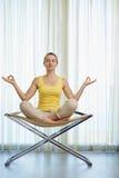 Het jonge vrouw mediteren op moderne stoel Stock Afbeelding