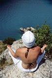 Het jonge vrouw mediteren op rotsen bij de rand van het water royalty-vrije stock afbeelding