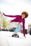 Het jonge vrouw met een skateboard rijden stock afbeelding