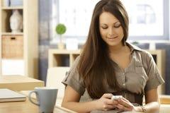 Het jonge vrouw mobiel gebruiken thuis Stock Fotografie