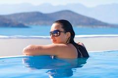 Het jonge vrouw ontspannen bij zwembad Royalty-vrije Stock Afbeelding