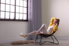 Het jonge vrouw ontspannen dichtbij venster met zonneblinden Ruimte voor tekst stock afbeeldingen