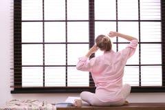 Het jonge vrouw ontspannen dichtbij venster met zonneblinden thuis royalty-vrije stock afbeelding