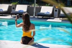 Het jonge vrouw ontspannen door de pool royalty-vrije stock fotografie