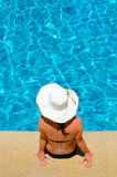 Het jonge vrouw ontspannen door de pool stock fotografie