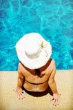 Het jonge vrouw ontspannen door de pool stock foto