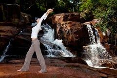 Het jonge vrouw ontspannen door de waterval stock afbeelding
