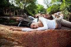 Het jonge vrouw ontspannen door de waterval stock afbeeldingen