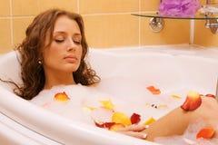 Het jonge vrouw ontspannen in een bad Stock Foto
