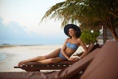 Het jonge vrouw ontspannen in een ligstoel op een tropisch strand bij zonsopgang of zonsondergang met modieuze strohoed, meisje o Royalty-vrije Stock Afbeelding