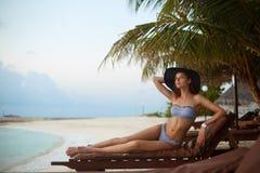 Het jonge vrouw ontspannen in een ligstoel op een tropisch strand bij zonsopgang of zonsondergang met modieuze strohoed, meisje o Royalty-vrije Stock Afbeeldingen