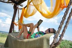 Het jonge vrouw ontspannen in hangmat stock foto's