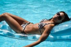 Het jonge vrouw ontspannen in het zwembad Stock Foto's